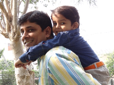 Boy playing on dad's shoulder