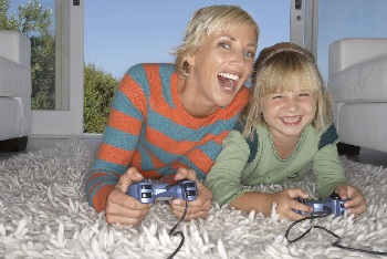 girl playing video game with mother